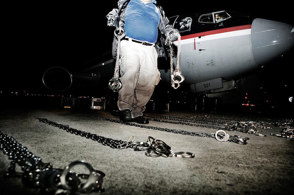 """Al igual que la película """"Conair"""" las cadenas están alineadas en el suelo antes de que los inmigrantes ilegales llegan al avión. Si alguno de ellos previamente han cometido un delito en los EE.UU. serán encadenados."""