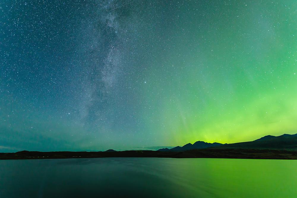 Milky Way and Aurora Borealis above the Alaska Range mountains at Round Tangle Lake along the Denali Highway in Interior Alaska. Autumn. Morning.