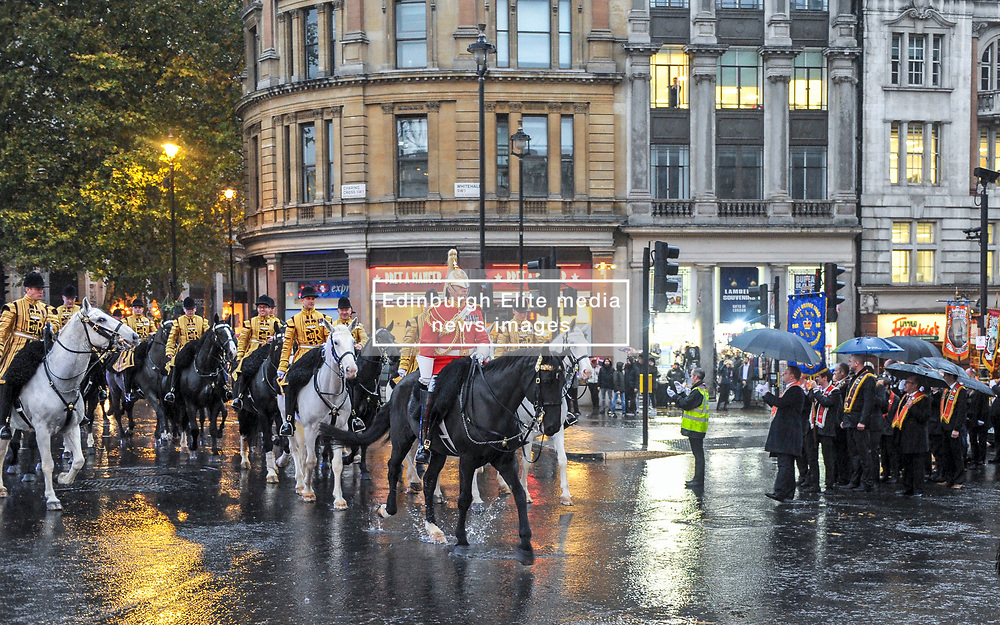 Orange men of the Orange order pause to let the mounted military pass by In Trafalgar Square after marching along Whitehall to lay wreaths at the Cenotaph London, 10 November 2018.