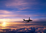 Airplane banks away over sunset lit clouds