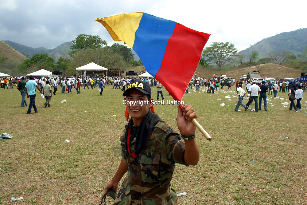 A former member of the paramilitary group Bloque Norte, or Northern Block, waves a flag after participating in a disarmament ceremony in Chimila, in northern Colombia, on March 8, 2006. An estimated 24,000 paramilitary members have turned in their weapons as part of a government negotiated peace deal. But some are skeptical if the government plan will really work and if the paramilitary members will be successful in their transformation to civilian life. (Photo/Scott Dalton)