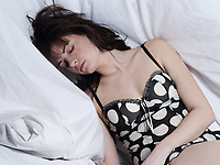 young woman in a white sheet bed on white background sleeping underneath sheets