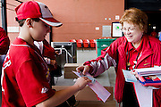 17 April 2010: A Busch Stadium greeter hands a pennant to a Cardinals fan entering Busch Stadium prior to the game between the St. Louis Cardinals and the New York Mets at  Busch Stadium in St. Louis, Missouri..