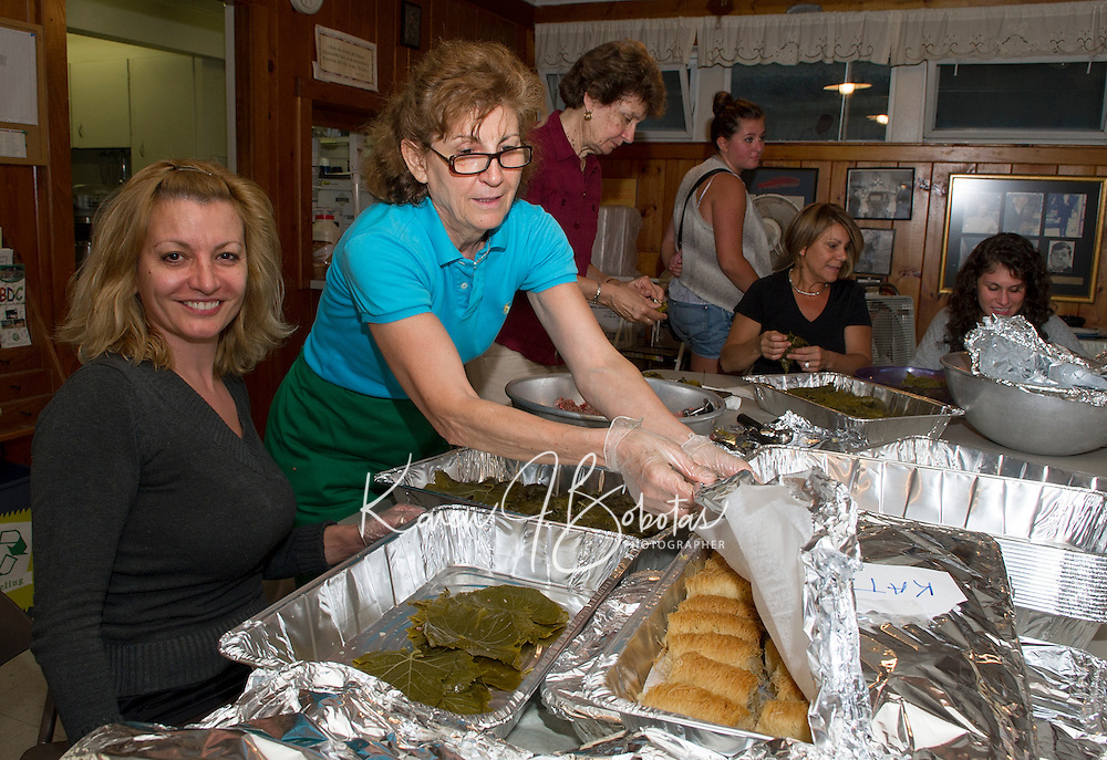 """Elena Kafanelis prepares """"Dolmathes"""" (stuffed grapes leaves) as Bessie Kafanelis covers the Kataifi pastries in preparation for the 26th annual Greek Summer Festival Saturday starting at 10am at the Taxiarchai Greek Orthodox Church in Laconia.  (Karen Bobotas/for the Laconia Daily Sun)"""