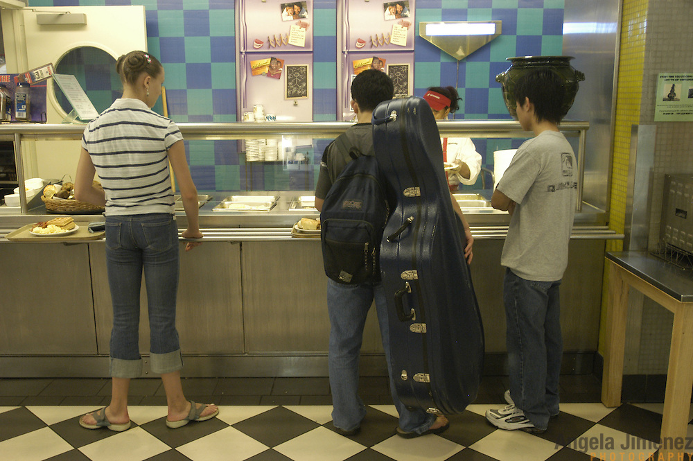 A young classical music student in the Pre-College Division program at The Juilliard School of music, center, waits in line for food at the cafeteria in between his weekly courses and lessons at the school, located at West 65th Street and Broadway in New York City, on Saturday, September 24, 2005. A dance student, left, waits next to him. Students audition for spots in the prestigious program, in which they can study until they graduate from high school.