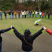People raise their hands during a memorial for Alpha Lake Rajai, 59, a homeless man known by many for regularly sitting on a bench in Ravenna Park. On March 8th he was shot and killed. Dozens of neighbors and friends came out to honor Rajai on Sunday, March 18, 2012 during the memorial, some saying he was a warrior that guarded their park. (Joshua Trujillo, seattlepi.com)
