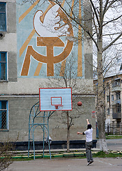 Man playing basketball on court in school with Soviet era hammer and sickle communist painting on wall at Yuzhno Sakhalinsk on Sakhalin Island Russia