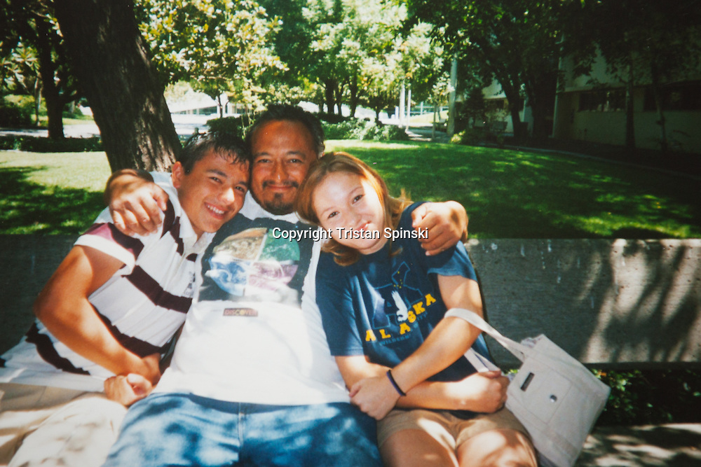 Photograph of Nick and Tiffany Martinez, right and left, sitting with their father, Donald Martinez, in Fresno, California 10 years ago. Tiffany's father suffers from schizophrenia, and is homeless in Fresno. His children, who hadn't seen him in years, tracked him down at a public library — a common sanctuary for the homeless population trying to avoid the summer heat and sun. Tiffany says her father recognized her, and for that she was grateful.