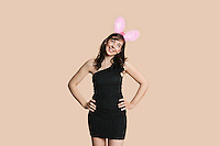 Beautiful young woman in black dress with bunny ears looking away over colored background