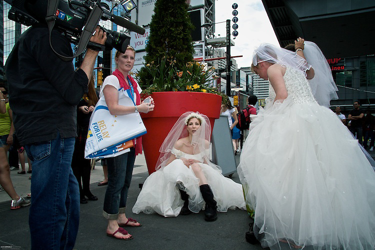 """Shooting in the hot 28C sun and speaking with the media and the public about The Relay for Life was hard work for the ladies in wedding gowns. The dresses are heavy and it's easy to work up a sweat in a matter of minutes. One """"bride"""" rests in the shelter of some shade. CCS: TBP May-20-2010"""