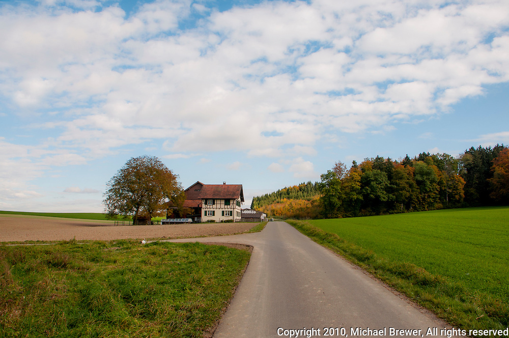 Vista of a lonely farmhouse in autumn amongst fields and bordering on a forest  near Aesch, Switerland.