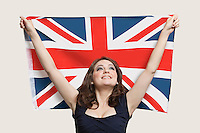 Young woman holding British Flag with pride over gray background