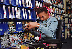 Young woman with Cerebral Palsy choosing video to buy in supermarket,