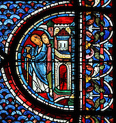 Men at the city gates, probably people listening to the preaching of Saint Maximin in Provence, from the Life of Mary Magdalene stained glass window, 13th century, in the nave of Chartres cathedral, Eure-et-Loir, France. Chartres cathedral was built 1194-1250 and is a fine example of Gothic architecture. Most of its windows date from 1205-40 although a few earlier 12th century examples are also intact. It was declared a UNESCO World Heritage Site in 1979. Picture by Manuel Cohen