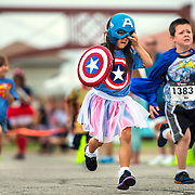 Bella Lynch, 6, of Lee's Summit, center, adjusted her Captain America mask while running in the 6-year-old division of the Kids Fun Run at Sunday's CASA SuperHero 5K Run/Walk, held at Town Center Plaza in Leawood on Sunday morning. Funds raised by the event will train and support more CASA (Court Appointed Special Advocate) volunteers to serve as the voice for abused and neglected children who are under court protection.
