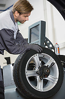 Cropped image of automobile mechanic repairing car's wheel in workshop