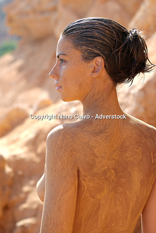 MR: Young attractive woman covered in mud on the beach