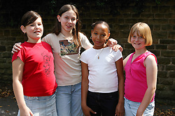 Four girls standing outside together,