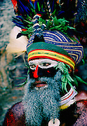 Bearded tribesman wearing war paints and feathered headdress during  a  Sing Sing gathering of tribes at Mount Hagen in Papua New Guinea