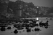 A flotilla of boats carries pilgrims and tourists past the ghats of the sacred Ganges at dawn.