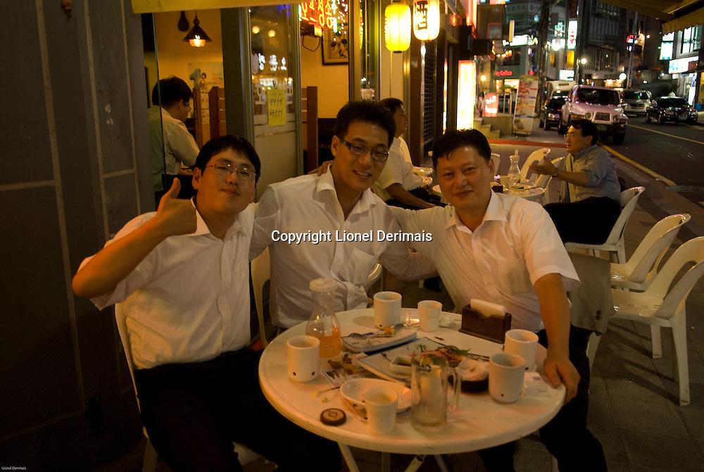 3 colleagues out for a meal and drinks in the business district Seolleung,  South Seoul, South Korea. 2009<br /> <br /> 3 collegues partagent un repas dans le quartier d'affaires de Seolleung, Seoul, Coree du Sud. 2009