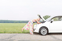 Full-length side view of woman examining broken down car on country road