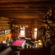 Num-Ti-Jah Lodge is surrounded by mountains and nestled next to Bow Lake, below Bow Glacier in Banff National Park, Alberta, Canada. Guests enjoy the common area of the lodge.