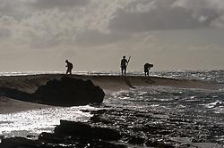 Beach walkers at Lae o Kaonohi near the Hanalei Colony Resort on the north shore of the island of Kauai in Hawaii.