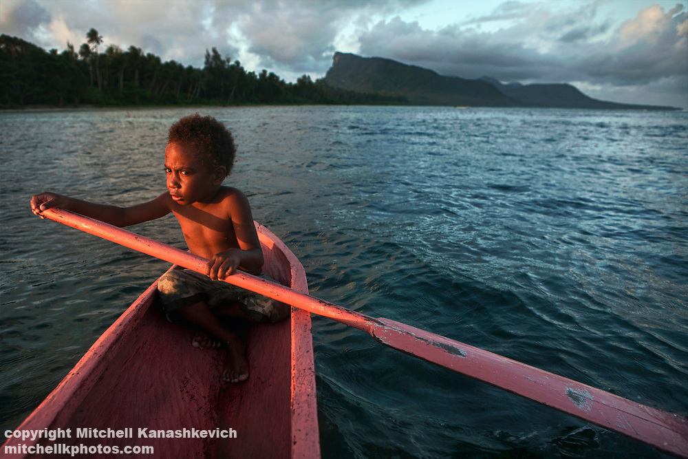 Young Ni Vanuatu boy trying to steer a canoe in the lagoon between the islands of Mota and Rah Lava. Rah Lava Island, Torba Province, Vanuatu