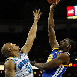 January 5, 2011; New Orleans, LA, USA; Golden State Warriors power forward Ekpe Udoh (20) shoots over New Orleans Hornets power forward David West (30) during the second half at the New Orleans Arena. The Warriors defeated the Hornets 110-103.  Mandatory Credit: Derick E. Hingle