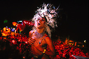 Transvestite in feather head-dress dancing in front of a crowd, Ibiza, 2000's