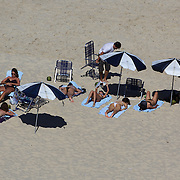 Sunbathers on Ipanema Beach, Rio de Janeiro, looking towards Arpoador point, Rio de Janeiro,  Brazil. 29th July 2010. Photo Tim Clayton.