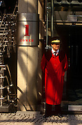 "A doorman in traditional long red overcoat stands outside the Lloyds of London address in the City of London, the capital's heart of the financial district. The post-modern architecture of the insurance underwriters Lloyd's building, home of the insurance institution Lloyd's of London which is located at number 1, Lime Street. Lloyd's is a British insurance market. It serves as a meeting place where multiple financial backers or ""members"", whether individuals (traditionally known as ""Names"") or corporations, come together to pool and spread risk. The Lloyds market began in Edward Lloyd's coffeehouse around 1688 and is today the world's leading insurance market providing specialist insurance services to businesses in over 200 countries and territories."