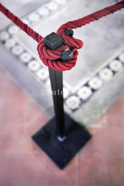 red museum rope protecting a floor grave