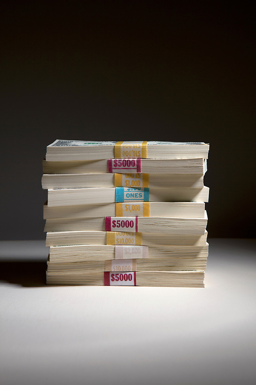 Side view of a stack of bundles of United States paper currency with $100 denominations on top