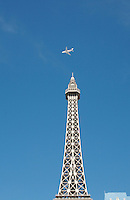 Airplane flys over replica Eifel Tower on Las Vegas Boulevard, Las Vegas, Nevada. Also known as The Las Vegas Strip where many of the famous themed casinos and hotels are located.