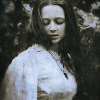 A monochromatic portrait of a girl in a vintage gown, with long hair, eyes closed and a dreamy/humble  expression.