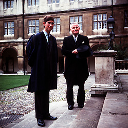File photo dated 08/10/67 of Prince Charles, wearing the Trinity gown of blue silk with black facings, accompanied by head porter, Mr Bill Edwards, posing on the steps of Neville Court, Cambridge University. The Prince has arrived in Cambridge to take up studies in Archaeology and Anthopology.