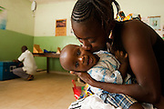 A mother kisses her child while they wait at the Kono government hospital in Koidu, Sierra Leone on Wednesday March 17, 2010.