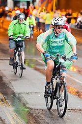 © Licensed to London News Pictures. 10/08/2014. Kingston, UK. The riders pass under John Lewis where crowds have taken shelter to cheer them on.  Cycling enthusiasts of all ages take part in the Prudential RideLondon cycling event through Kingston Upon Thames, Surrey in heavy rain today 10th August 2014. RideLondon is an annual two-day festival of cycling and part of the legacy of the 2012 Olympic Games. Photo credit : Stephen Simpson/LNP