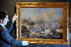 © Licensed to London News Pictures. 23/01/2012, London, UK. An employee straightens 'Winter Landscape with Figures by Dutch Artist Frederik Marinus Kruseman (1816-1882) estimated to fetch 70,000-90,000GBP. Photo call at Bonhams auctioneers in Central London for 19th Century Paintings sale.  Photo credit : Stephen Simpson/LNP