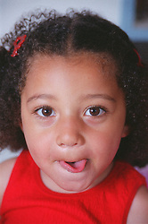 Portrait of young girl sticking tongue out,