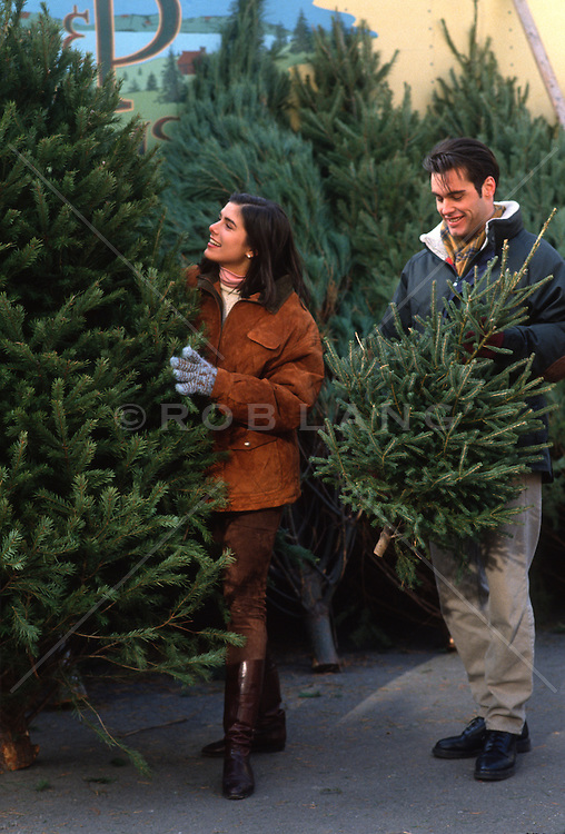 Couple at a Christmas Tree stand picking out a tree
