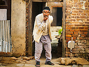 01 MARCH 2017 - KHOKANA, NEPAL: A man stands in the doorway of his home, damaged in the 2015 earthquake. Recovery seems to have barely begun nearly two years after the earthquake of 25 April 2015 that devastated Nepal. In some villages in the Kathmandu valley workers are working by hand to remove ruble and dig out destroyed buildings. About 9,000 people were killed and another 22,000 injured by the earthquake. The epicenter of the earthquake was east of the Gorka district.     PHOTO BY JACK KURTZ