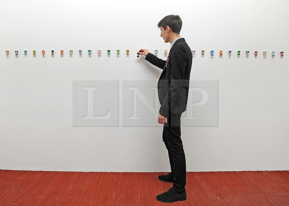 © licensed to London News Pictures. LONDON, UK.  22/06/11. Printmaker Henrik Potter positions one his pieces in his artwork 'Medals' consisting of 50 paper medals. Students present their work at The Royal College of Art's Fine Art Graduate Show 2011. The show runs from 24th June-3rd July 2011. Mandatory Credit Stephen Simpson/LNP