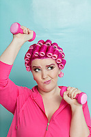 Young woman making face while lifting dumbbell over colored background