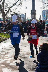 London, February 17th 2015. Members of Parliament put their dignity aside for a bit of fun as they compete in the annual Parliamentary Pancake Race in Victoria Tower Gardens adjacent to the House of Lords.  PICTURED: Lord Redesdale and Patrick Wintour of the Guardian.