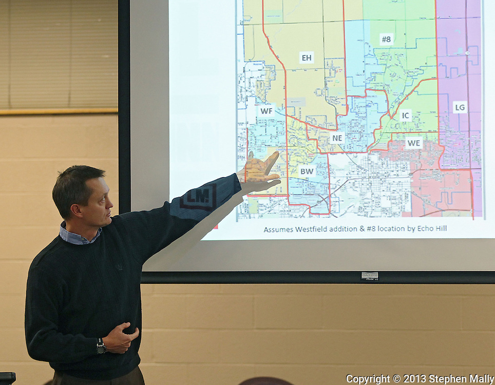 Boundary Committee member Derek Jensen of Marion points to a map as he delivers his section of the report during a Linn-Mar Community School District Board of Education meeting at the Linn-Mar Learning Resource Center in Marion on December 9, 2013.