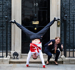 © Licensed to London News Pictures. 04/06/2018. London, UK. Gold medal winning gymnast Dominick Cunningham (L) performs a handstand with Sports Minister Tracey Crouch MP (R) outside 10 Downing Street. Photo credit: Rob Pinney/LNP