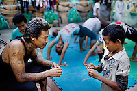 """Tuy Sobil, 34, or known as """"KK,"""" mediates a disagreement between Bunthoern Nganh, 14, a dancer, at right, and another boy, at the youth center, in Phnom Penh, Cambodia, on Wednesday, April 21, 2010. The center provides mentoring and educational classes, along with hip-hop music writing and breakdancing classes, for at-risk youth."""